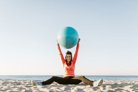 Woman doing sports with gym ball early in the morning on the beach