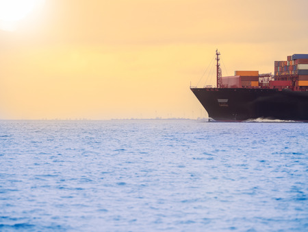 Germany, near Cuxhaven, North Sea, container ship at sunset