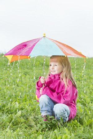 Young girl crouching with umbrella on meadow, rainy weather LANG_EVOIMAGES
