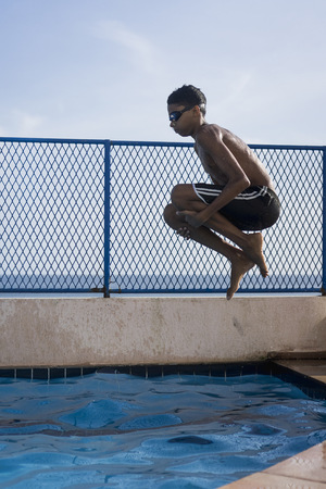 Teenage boy doing a cannonball dive into swimming pool LANG_EVOIMAGES