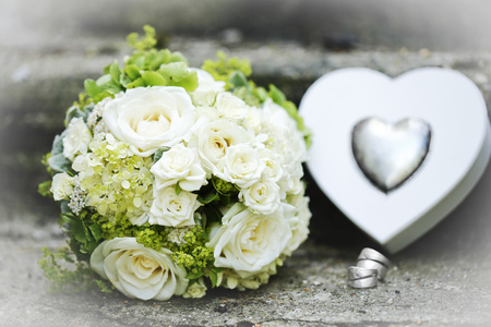White bridal bouquet, wedding rings and heart can