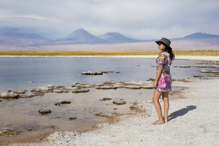 edge: Chile, San Pedro de Atacama, woman standing in the desert at lakeside LANG_EVOIMAGES