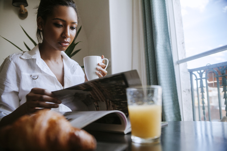 turning the page: Portrait of young woman reading magazine at breakfast table LANG_EVOIMAGES