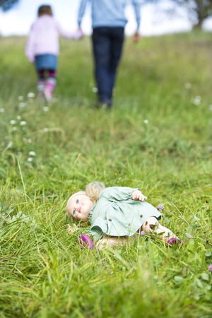 Doll lying on meadow while man going away with little girl LANG_EVOIMAGES