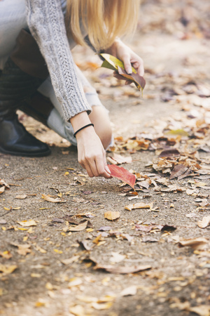 discolored: Teenage girl collecting autumn leaves
