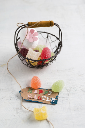Happy Easter tag on basket with jelly eggs