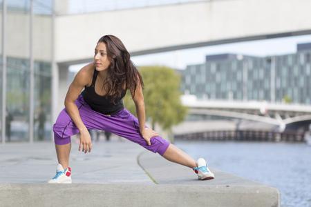 Young woman exercising at riverside