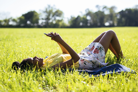 Young woman relaxing on a meadow using smartphone