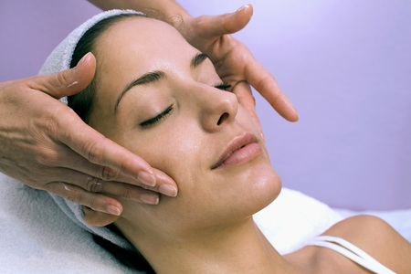 Mujer joven que recibe el masaje facial, ojos cerrados, primer plano LANG_EVOIMAGES