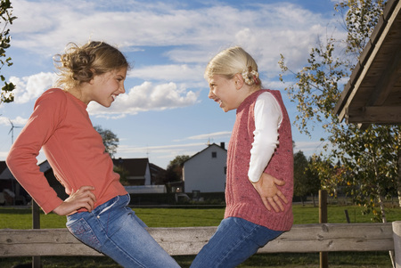 Two Girls (8-11) On Wooden Railing, Hand On Hip, Side View LANG_EVOIMAGES