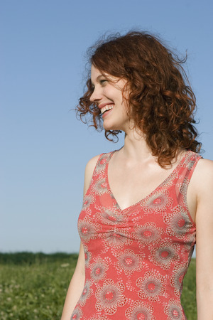 Young Woman Standing In Meadow, Smiling LANG_EVOIMAGES