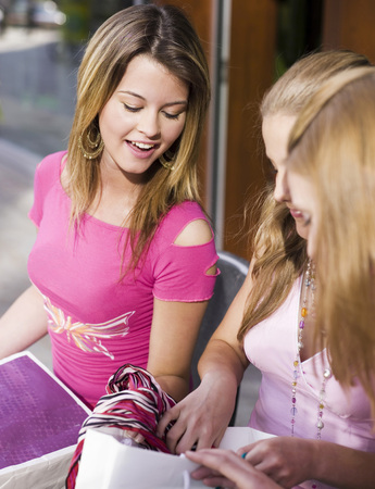 Teenage Girls Look Into Shopping Bags, Smiling LANG_EVOIMAGES
