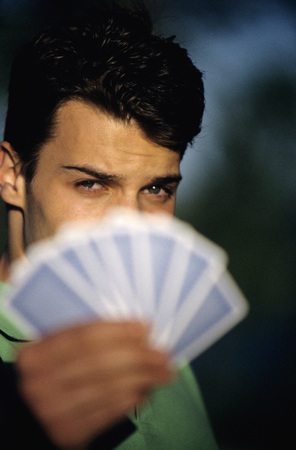 Young Man Holding Playing Cards, Focus On Man At Background, Close-Up LANG_EVOIMAGES