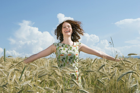Young Woman Standing In Cornfield, Arms Out, Smiling LANG_EVOIMAGES