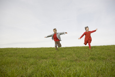Boy (10-12) And Girl (7-9) Running In Meadow, Arms Outstretched