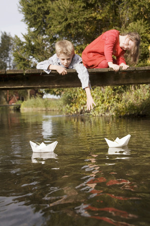 Boy (10-12) And Girl (7-9) On Bridge, Watching Paper Boats In Water