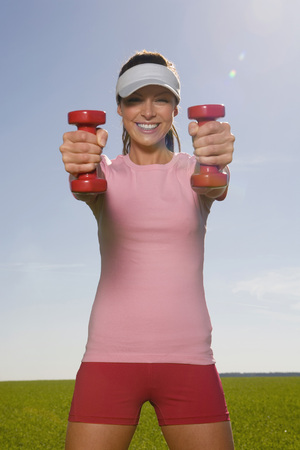 Young Woman Exercising With Dumbbells, Smiling