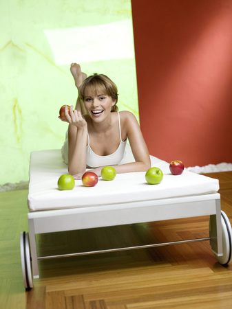 Woman Lying On Bed With Apples LANG_EVOIMAGES