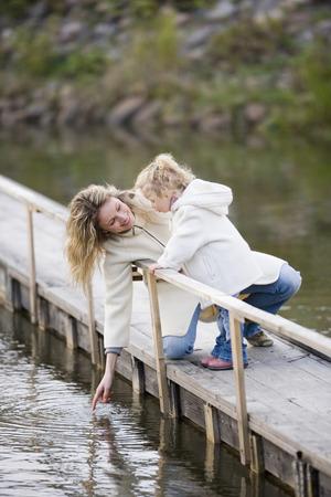 arrodillarse: Madre con hija en el embarcadero LANG_EVOIMAGES