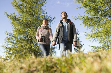 Young Couple Walking In Meadow, Hand In Hand