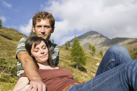 Young Couple Sitting In Meadow In Mountains
