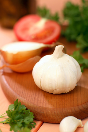 Sliced Tomato, Onion, Garlic And Parsley On Chopping Board LANG_EVOIMAGES