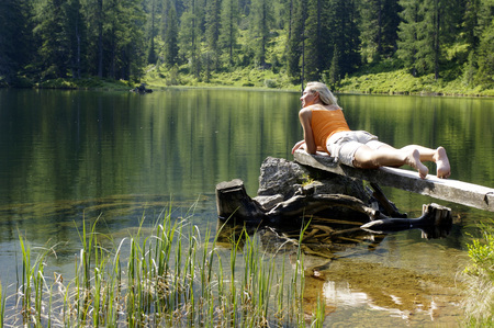 Young Woman Lying On Wooden Plank At Lake LANG_EVOIMAGES