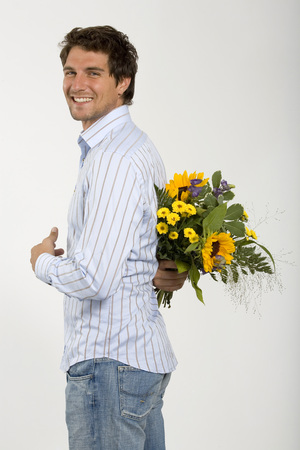 Young Man Holding Bouquet Of Flowers Behind Back,Smiling,Close-Up,Portrait LANG_EVOIMAGES