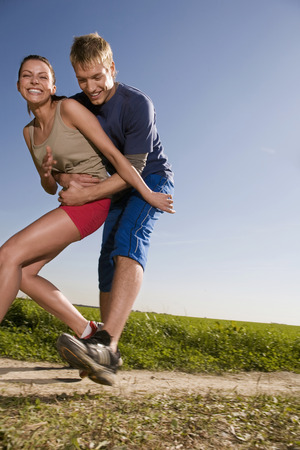 in low spirits: Young Couple Jogging, Man Catching Woman LANG_EVOIMAGES