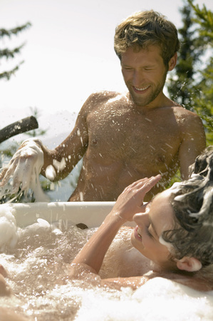 Young Couple, Woman Lying In Bathtub, Splashing, Outdoors