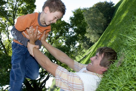 Father Lying On Grass And Holding Up Son (4-7), Smiling
