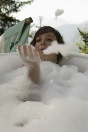 Young Woman Lying In Bathtub, Blowing Suds, Outdoors