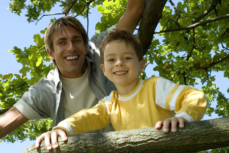 Father And Son (4-7) Sitting On Tree, Close-Up LANG_EVOIMAGES