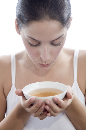 lose up: Young Woman Holding Tea Bowl, Close-Up LANG_EVOIMAGES