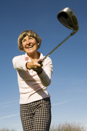 Germany, Bavaria, Ammersee, Senior Woman Swinging Golf Club, Smiling, Low Angle View LANG_EVOIMAGES