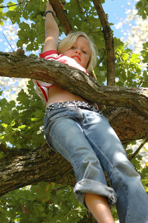 Girl (7-9) Climbing On Tree, Low Angle View
