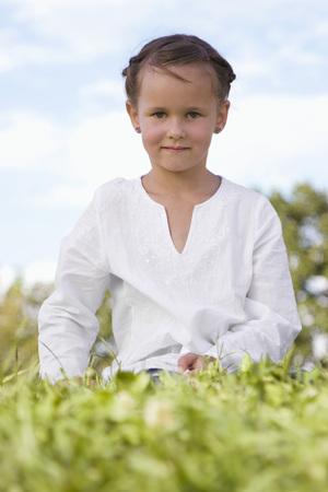 Girl (7-9) Sitting In Meadow