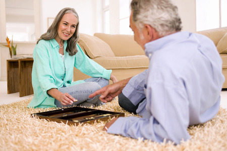 relaciones sexuales: Mature Couple Playing Backgammon In Living Room,Smiling