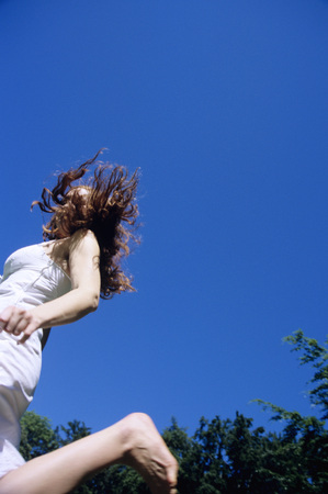 in low spirits: Young Woman Jumping, Smiling, Low Angle View
