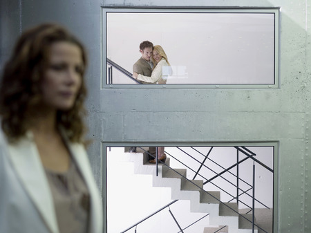 Couple Embracing On Staircase, (Focus On Background) LANG_EVOIMAGES