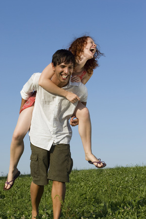 closed community: Man Giving Woman Piggyback In Meadow, Laughing