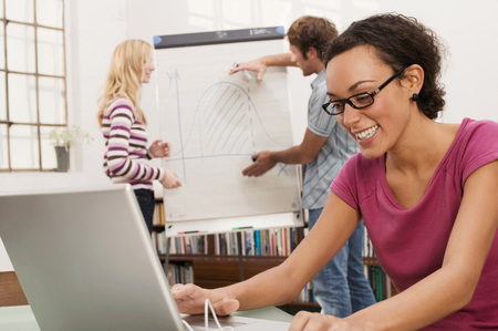 technolgy: Young Man Explaining Woman Chart In Background, Focus On Woman Using Laptop, Smiling LANG_EVOIMAGES