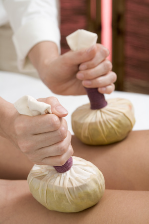 Woman Receiving Herbal Stamp Massage, Mid Section