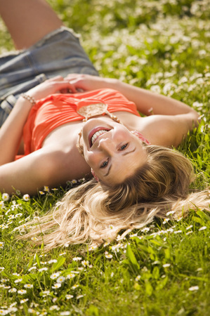 Young Woman Lying In Meadow, Smiling
