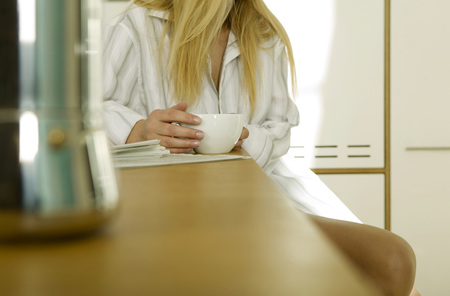 furniture part: Young Woman Sitting In Kitchen With Cup Of Coffee,Mid Section