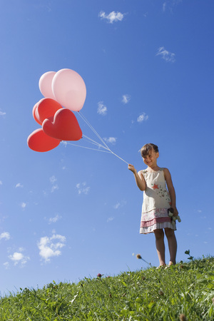 Girl (7-9) Holding Bunch Of Ballons LANG_EVOIMAGES