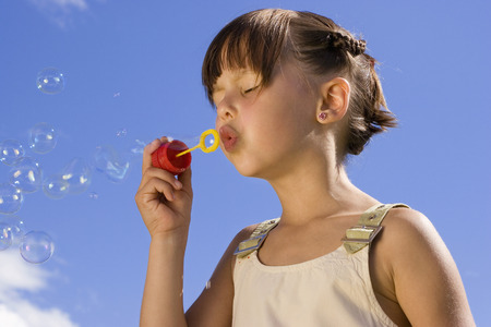 Girl (7-9) Blowing Soap Bubbles, Eyes Closed, Close-Up LANG_EVOIMAGES