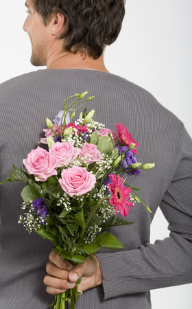 give out: Young Man Holding Bouquet Of Flowers Behind Back,Smiling,Close-Up LANG_EVOIMAGES