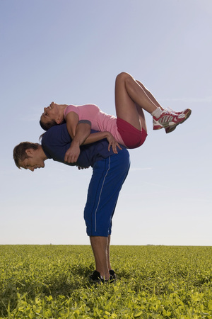 Young Couple Exerting Gymnastic On Meadow, Side View LANG_EVOIMAGES