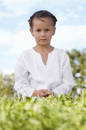 Girl (7-9) Sitting In Meadow